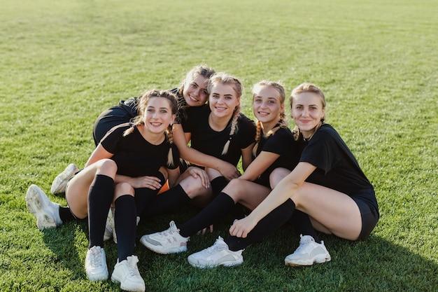 Lächelnde sportive frauen der vorderansicht, die fotografen betrachten