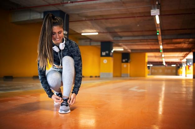Lächelnde sportlerin, die ihren schnürsenkel bindet und sich auf das training vorbereitet