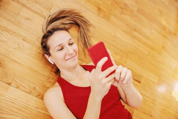 Lächelnde sportlerin, die sich zu hause auf den boden legt und das telefon zum aufhängen in sozialen medien verwendet using