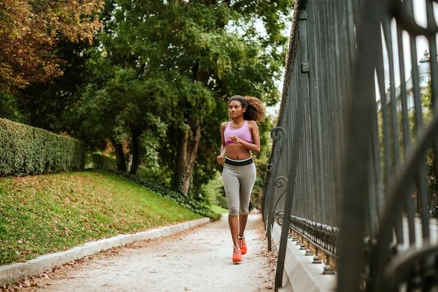 Lächelnde sportliche frau der junge, die morgens in park läuft.