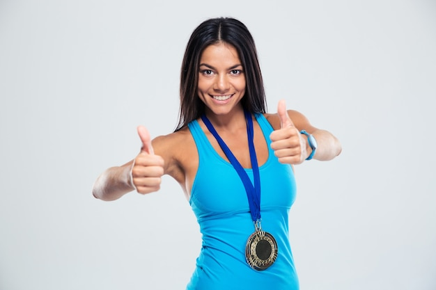 Lächelnde sportliche frau, die daumen hoch zeichen zeigt