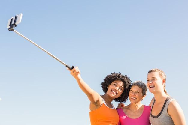 Lächelnde sportliche frauen, die selfies mit selfiestick nehmen