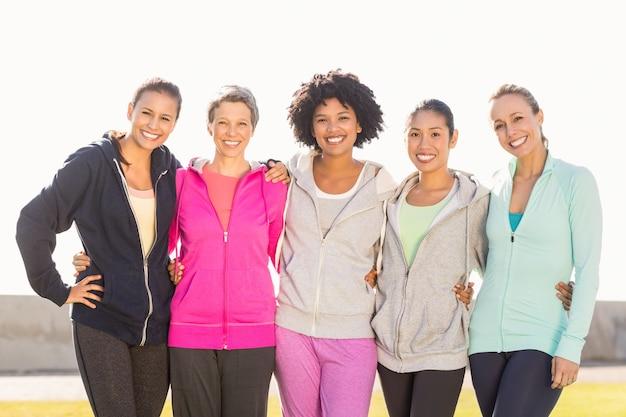 Lächelnde sportliche frauen mit den armen um einander
