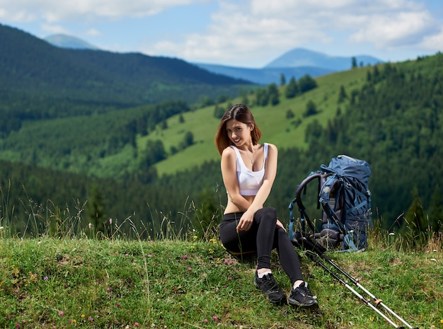 Lächelnde sportliche reisende mit rucksack und trekkingstöcken, die auf einem gras sitzen, sich auf einem hügel ausruhen und den sommertag in den bergen genießen. speicherplatz kopieren