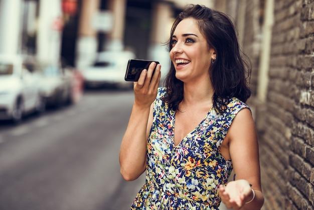 Lächelnde sprachanmerkung der aufnahme der jungen frau in ihrem intelligenten telefon