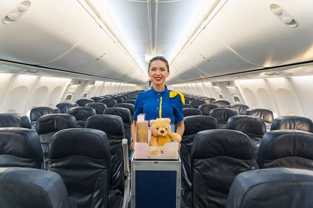 Lächelnde stewardess führt trolley mit geschenken