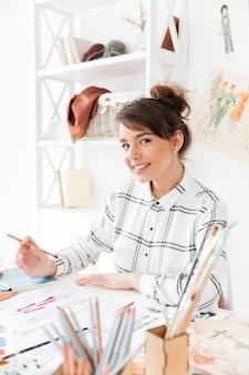 Lächelnde stilvolle designerin, die an ihrem schreibtisch sitzt