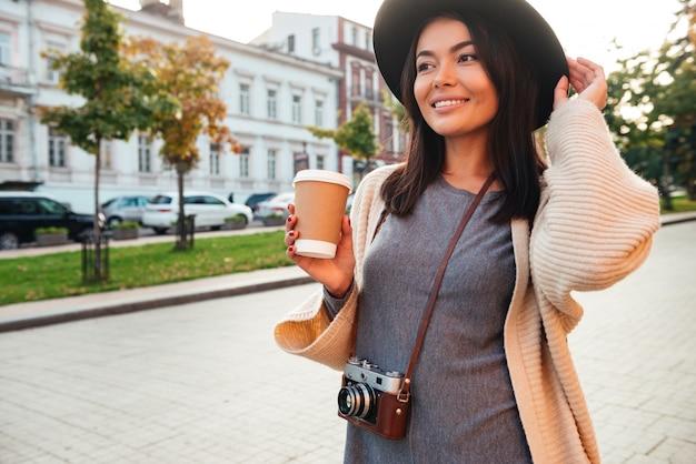Lächelnde stilvolle frau, die kaffeetasse hält
