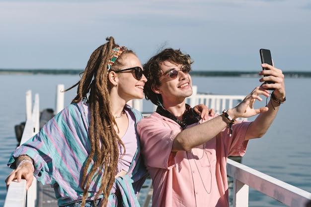 Lächelnde stilvolle freunde mit sonnenbrille, die auf dem pier stehen und ein selfie auf dem smartphone machen