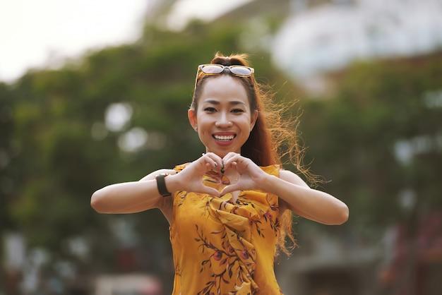 Lächelnde stilvolle junge asiatin, die herzgeste zeigt
