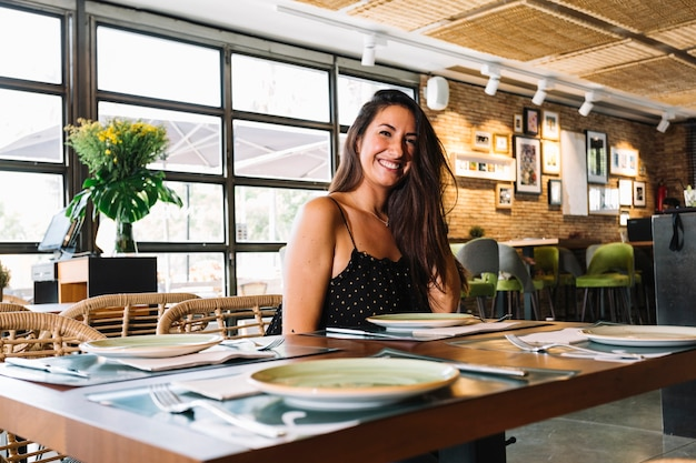Lächelnde stilvolle junge frau, die im restaurant sitzt