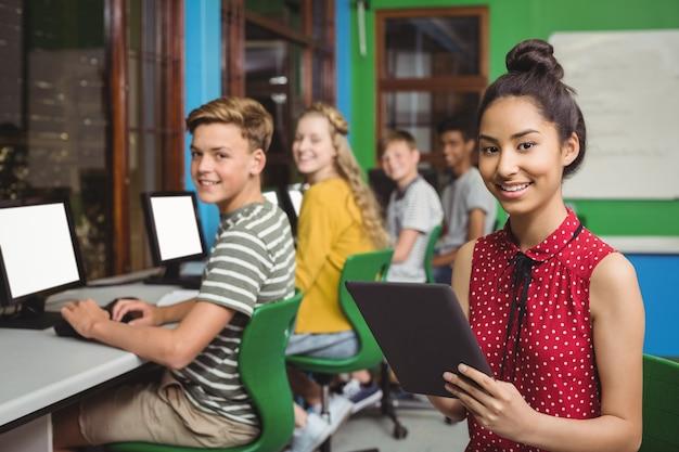 Lächelnde studenten, die auf digitalem tablet und computer im klassenzimmer studieren