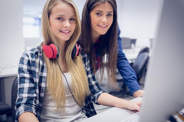 Lächelnde studenten, die computer an der universität verwenden