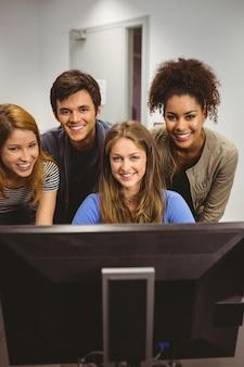 Lächelnde studenten, die den computer zusammen betrachtet kamera verwenden