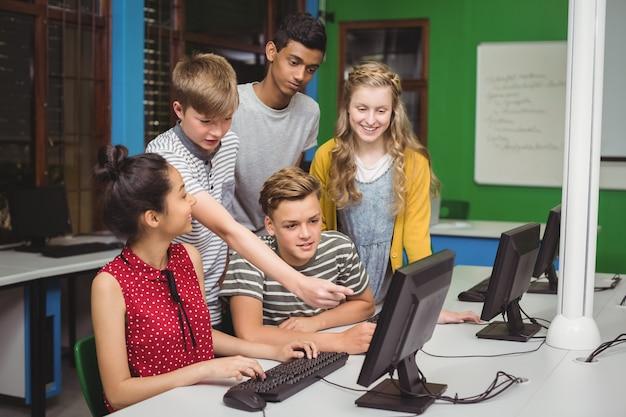 Lächelnde studenten, die im computerklassenzimmer studieren