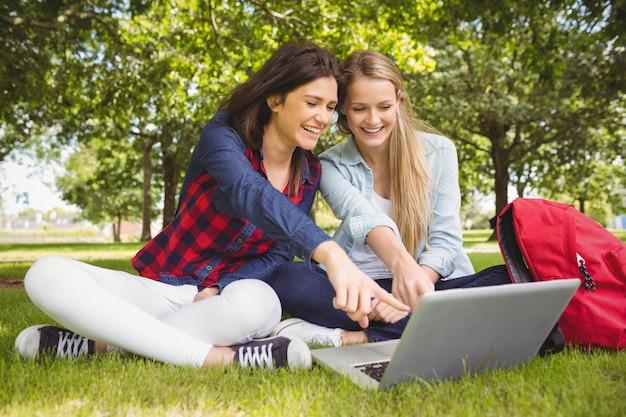 Lächelnde studenten, die laptop am park verwenden