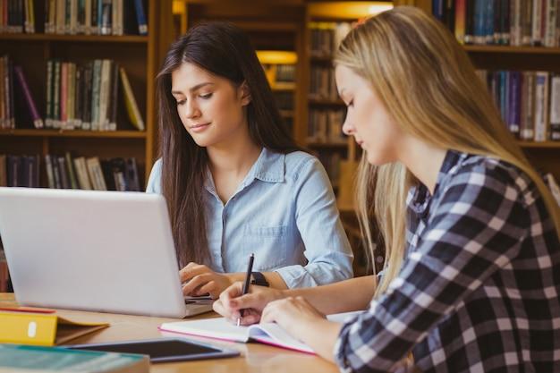 Lächelnde studenten, die laptop in der bibliothek verwenden