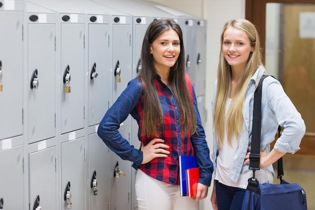 Lächelnde studenten, die nahe schließfach an der universität aufwerfen