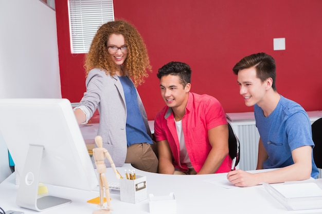Lächelnde studenten, die zusammen an computer arbeiten