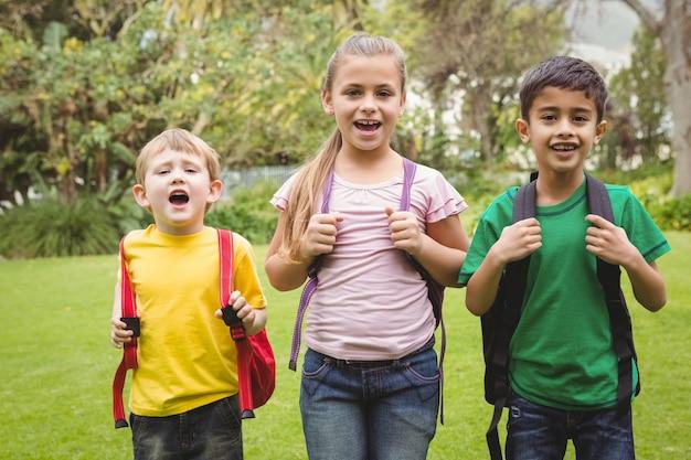 Lächelnde studenten, die zusammen mit schultaschen stehen