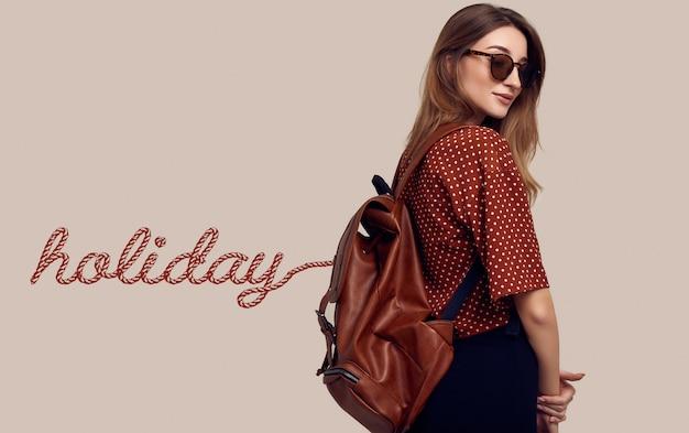 Lächelnde studenten-hipster-frau mit rucksack, der in den urlaub geht