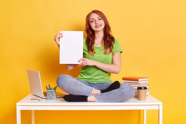 Lächelnde studentin, die auf tisch sitzt und leeres papierhemd in den händen hält