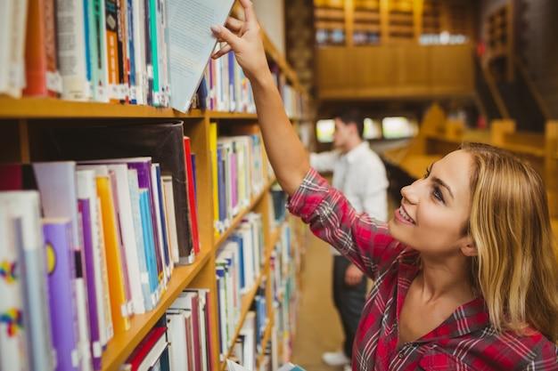 Lächelnde studentin, die buch in der bibliothek nimmt