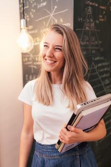 Lächelnde studentin, die einen laptop vor einer tafel hält