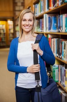 Lächelnde studentin, die in der bibliothek an der universität aufwirft