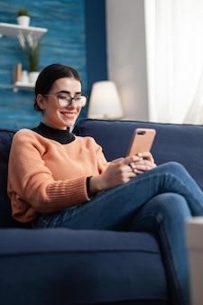 Lächelnde studentin, die sich auf der couch entspannt, während sie mit ihren freunden über eine nachricht über die kommunikation in den sozialen medien spricht. teenager-frau, die mit einem mobilen app-gerät im sozialen netzwerk chattet