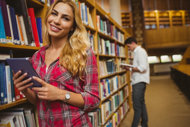 Lächelnde studentin, die tablette in der bibliothek verwendet