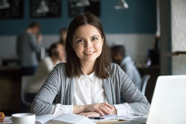 Lächelnde studentin, welche die kamera sitzt am cafétisch betrachtet