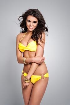Lächelnde süße frau im gelben bikini