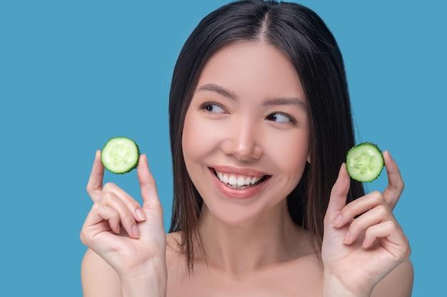 Lächelnde süße junge frau hält scheiben der gurke
