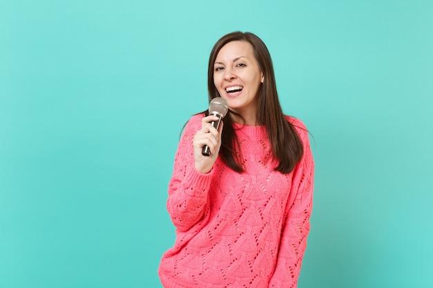 Lächelnde süße junge frau in gestricktem rosa pullover, die in der hand hält und lied im mikrofon singt, isoliert auf blau-türkisfarbenem wandhintergrund, studioporträt. menschen lifestyle-konzept. kopieren sie platz.