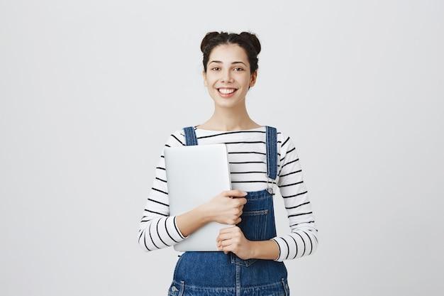 Lächelnde süße junge programmiererin, teenager-mädchen beginnen zu codieren, laptop halten und zufrieden aussehen