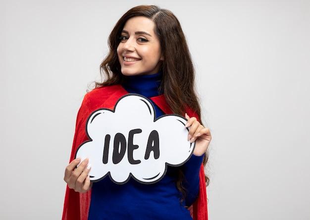 Lächelnde superfrau mit rotem umhang hält ideenblase, die vorne auf weißer wand lokalisiert betrachtet