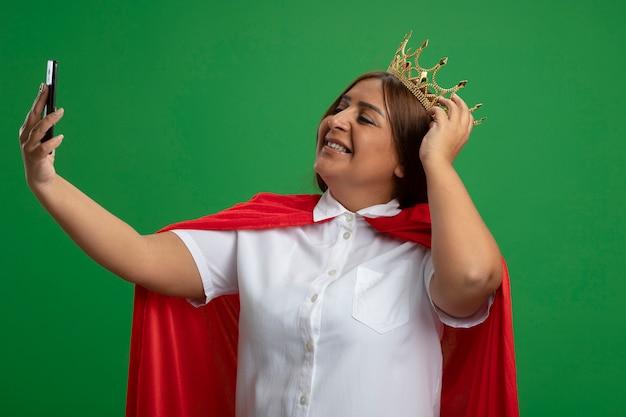 Lächelnde superheldenfrau mittleren alters, die krone trägt, nehmen ein selfie, das hand auf krone lokalisiert auf grün setzt