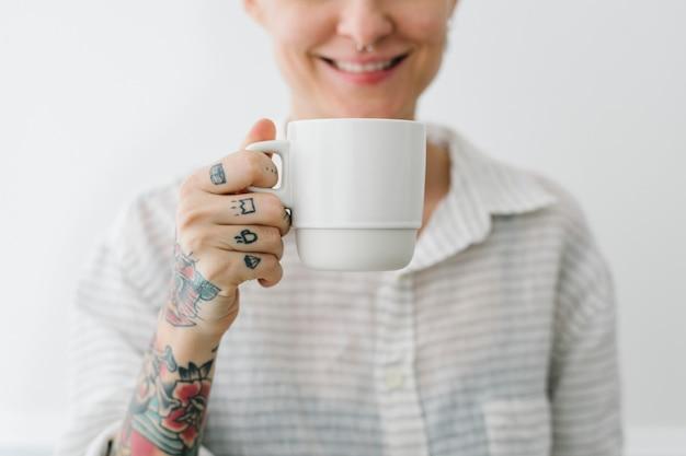 Lächelnde tätowierte frau, die eine tasse kaffee trinkt