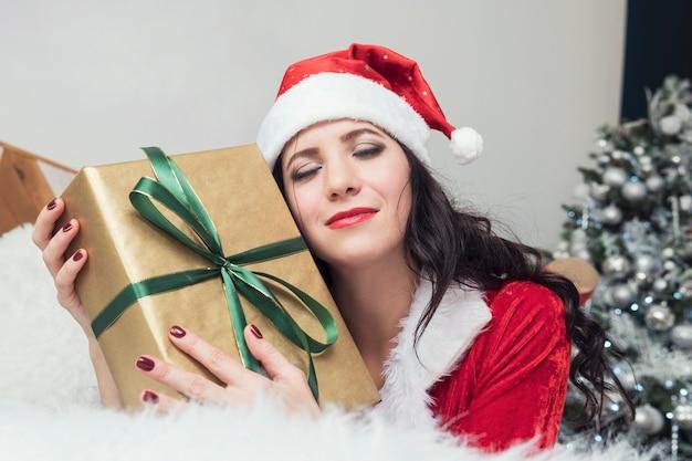 Lächelnde teenager-mädchen in sankt-helfer-hut mit vielen geschenkboxen auf weißem hintergrund. positives emotionales sankt-mädchen. konzept des verkaufs und der weihnachtseinkäufe. weihnachten. mädchen, das geschenke umarmt.