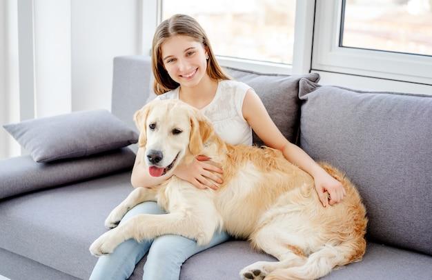 Lächelnde teenager-mädchen mit entzückenden hund im hellen raum