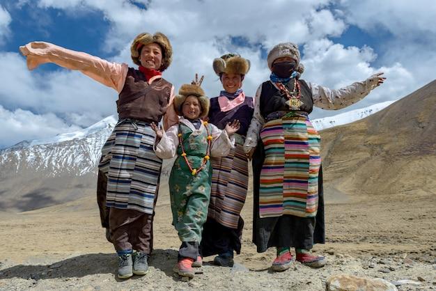 Lächelnde tibetanische alte frauen und ihre familie im nationalen bunten kleid, das auf dem sommergebiet in tibet bleibt