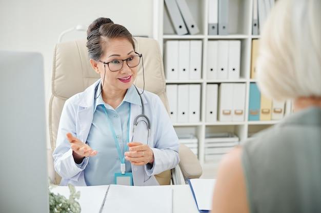 Lächelnde tochter, die mit patient spricht