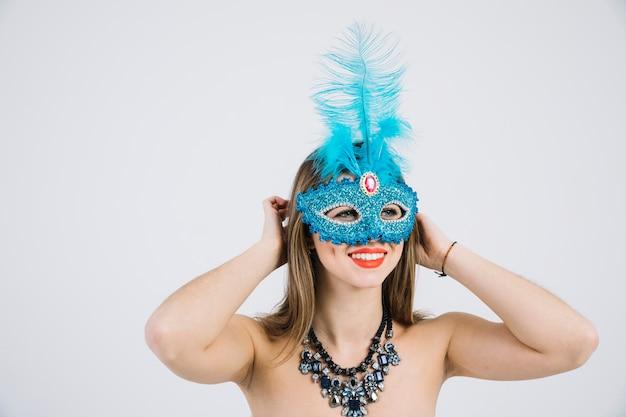 Lächelnde topless frau, die maskeradekarnevalsmaske und -halskette trägt