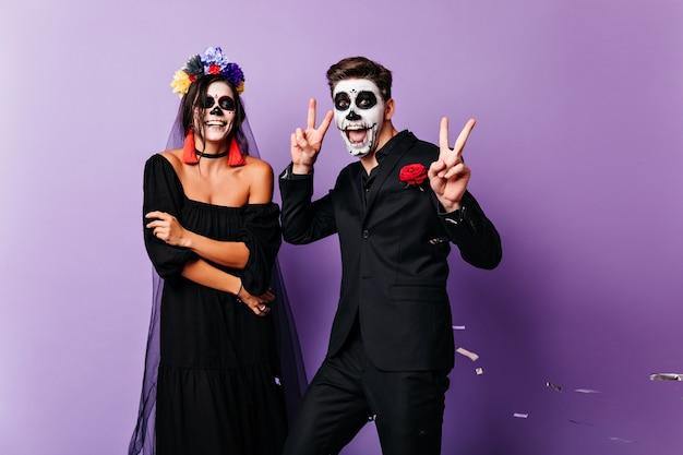 Lächelnde tote braut, die auf lila hintergrund aufwirft. paar zombies tanzen zusammen.