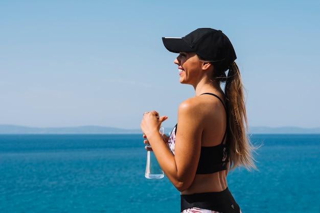 Lächelnde tragende kappe der jungen frau, die in der hand vor dem meer wasserflasche halten steht