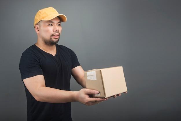 Lächelnde tragende kappe des hübschen asiatischen lieferers, paket, pappschachtel, beweglicher haustag und eilzustellungskonzept gebend und tragen