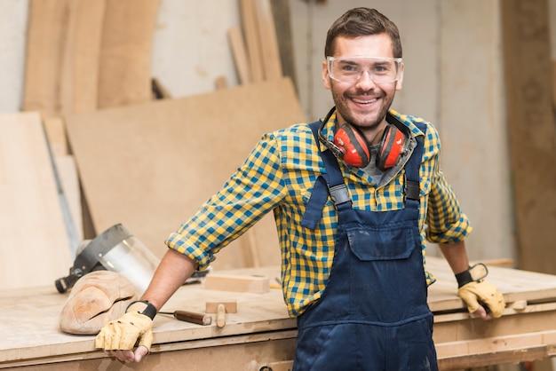 Lächelnde tragende sicherheitsgläser des heimwerkers, die kamera betrachten