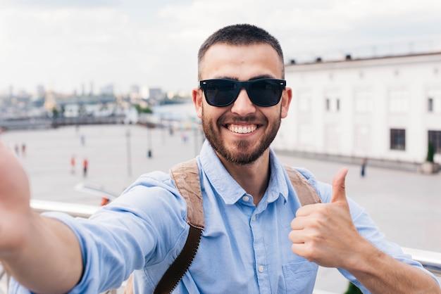 Lächelnde tragende sonnenbrille des jungen mannes, die selfie nimmt und daumen herauf geste zeigt