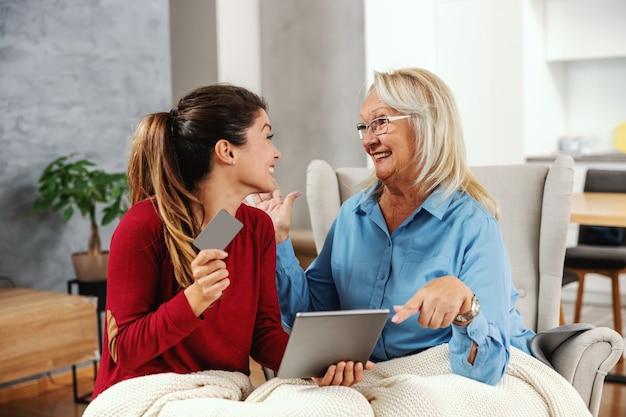 Lächelnde, überglückliche mutter und tochter, die zu hause sitzen und tablet für online-einkäufe verwenden. tochter hält tablette und kreditkarte.
